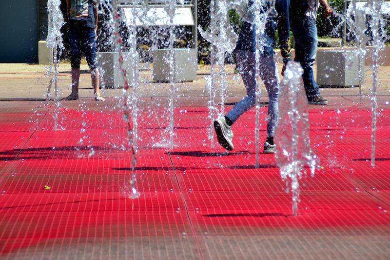 Kinderfüße in einem Springbrunnen; der Grund ist rot