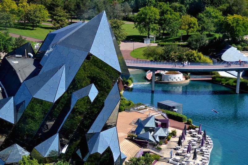 Der gläserne Kristall, das Wahrzeichen von Futuroscope, von oben; rechts die tiefblaue Lagune des Parks