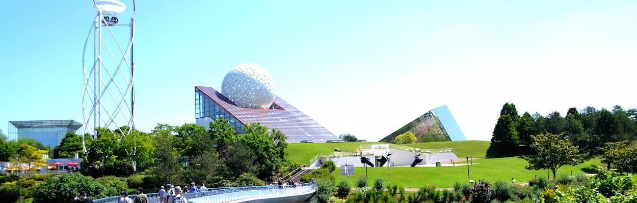 Blick über eine geschwungene Brücke hinüber zu den geometrisch aussehenden Pavillons von Futuroscope