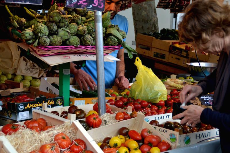 Paris-Impressionen: eine Dame zahlt an einem Gemüsestand ihre Einkäufe / Markt an der Bastille