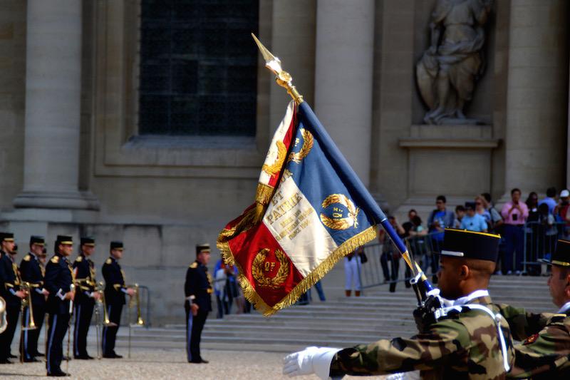 Paris-Impressionen: Soldaten tragen die französische Flagge bei einer Zeremonie am Invalidendom