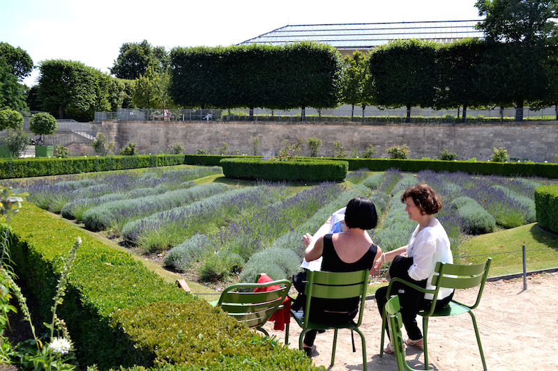 Paris-Impressionen: zwei Damen sitzen vor einem Beet mit Lavendel in den Tuilerien