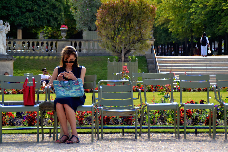 Paris-Impressionen: eine Dame sitz auf einem Stuhl im Jardin du Luxembourg und tippt auf ihrem Smartphone