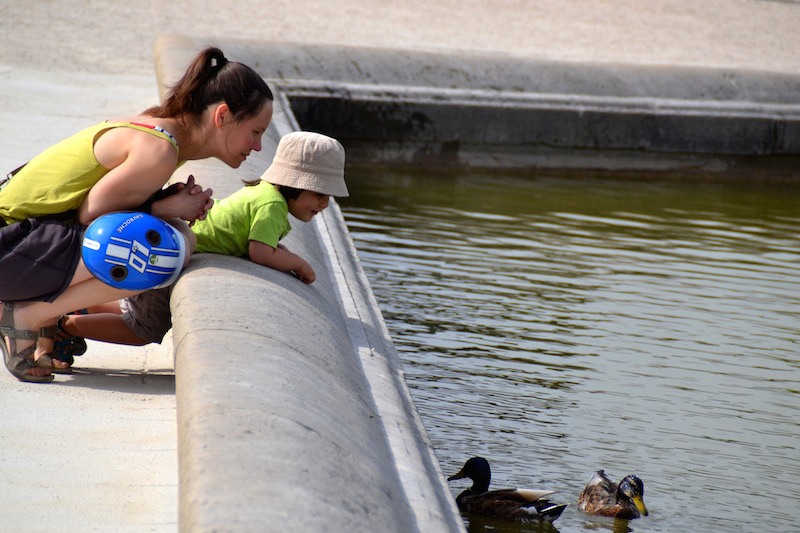Paris-Impressionen: Mutter und kleines Kind betrachten Enten im Teich des Jardin du Luxembourg