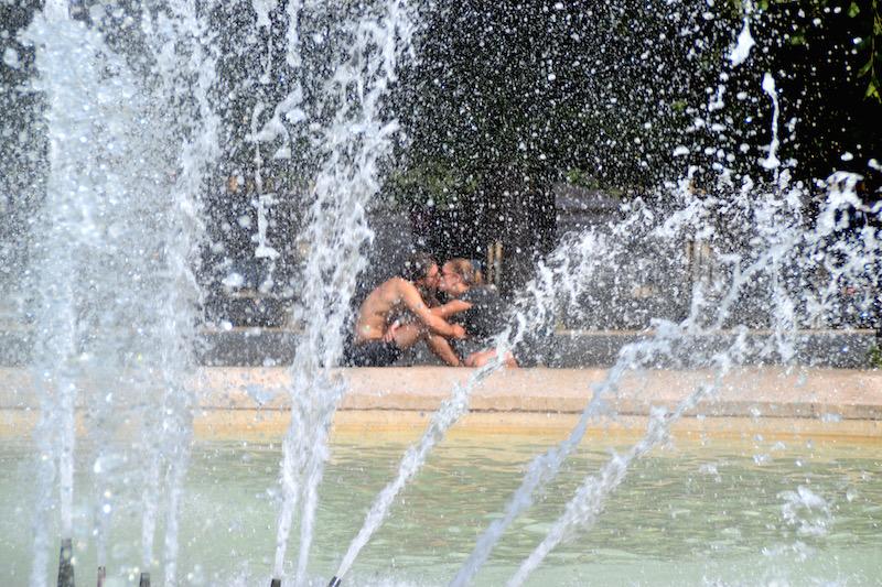 Paris-Impressionen: ein sich küssendes Paar hinter einem Springbrunnen am Palais Royal