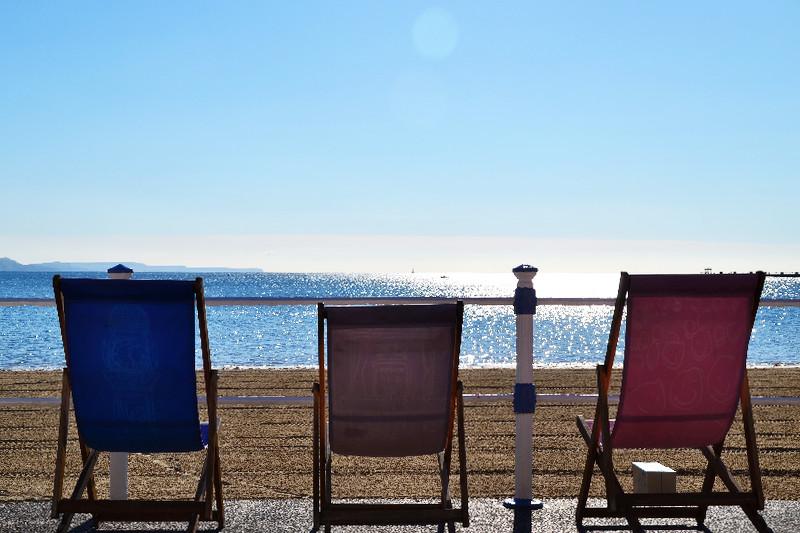 Strandstühle an der sonnigen Promenade von Weymouth