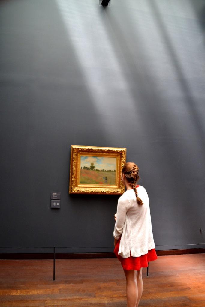 Eine junge Frau betrachtet ein Gemälde von Monet im Musée d'Orsay