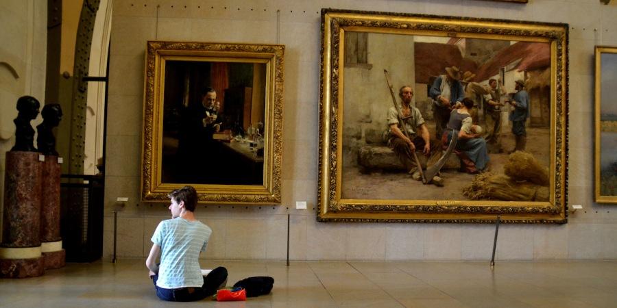 Ein Junge zeichnet vor einem Gemälde im Musée d'Orsay in seinem Zeichenblock