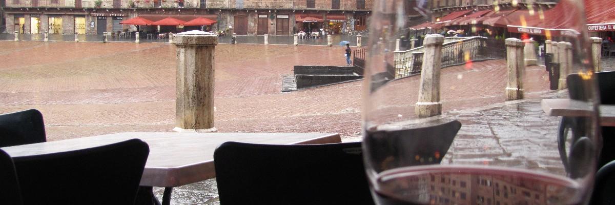 Entspanntes Reisen: mit einem Weinglas in einem Café in Siena