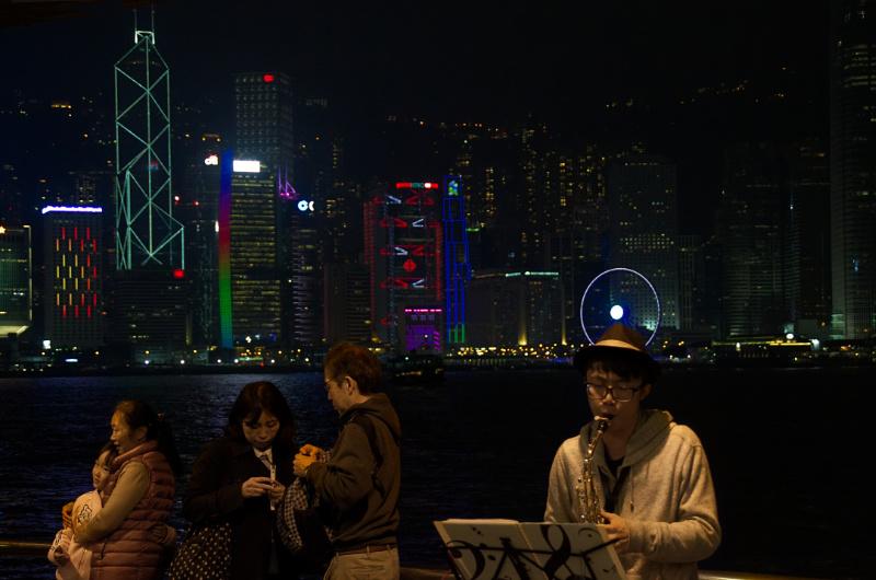 Hongkong: Straßenmusiker und Touristen vor der Skyline