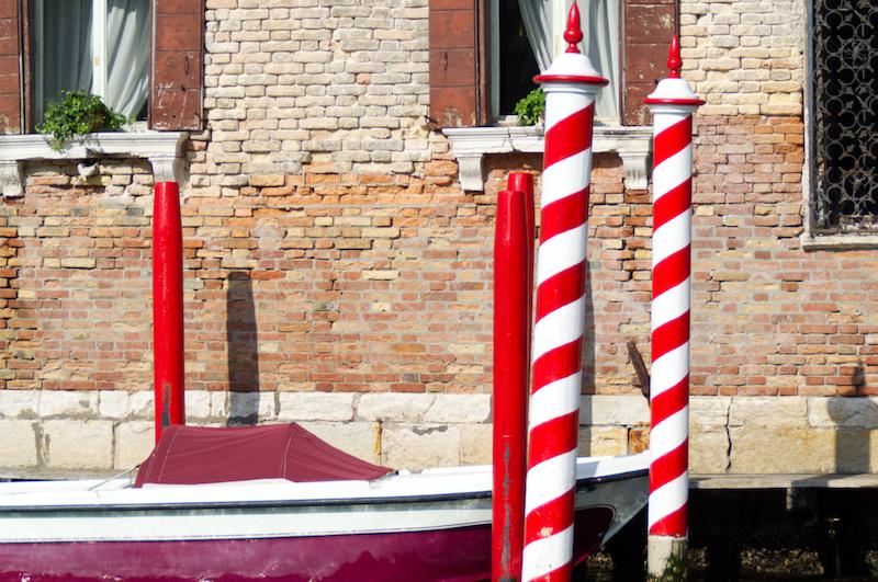 Venedig: Rot-Weiße Pfäle vor Häuserfassade am Canal Grande
