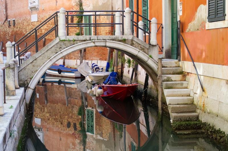 Venedig: Im Wasser eines stillen Kanals spiegeln sich Brücke, Häuserfassaden und Boote