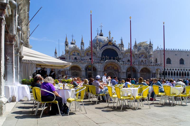 Venedig: Café mit gelben Stühlen auf dem Markusplatz