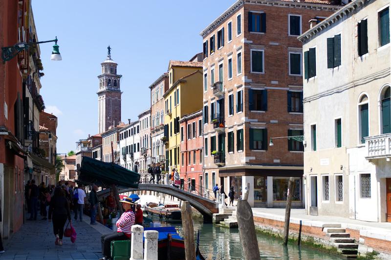 Venedig: Markt an einem der Kanäle, dahinter ein schiefer Kirchturm