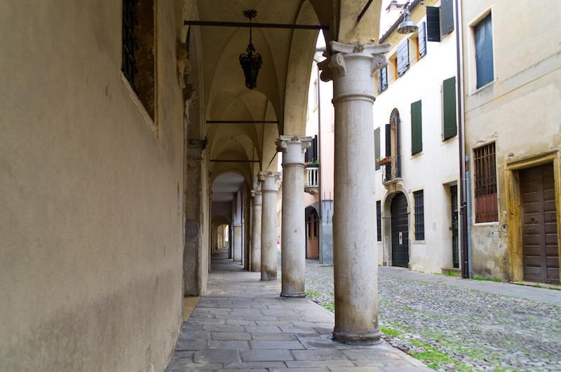 Padua: Arkadengang mit dicken Säulen und Lampen, die an der Decke hängen