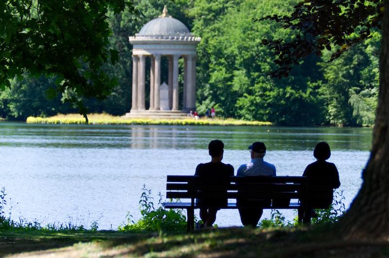 Besucher rasten auf einer Parkbank mit Blick aufs Monopteros im Schlosspark Nymphenburg