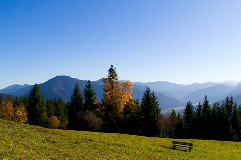Bergwiese mit Bank und bunten Bäumen am Tegernsee