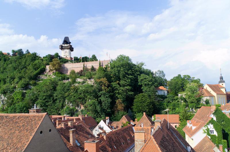 Die Dächer der Altstadt von Graz un der Kalvarienberg mit Uhrturm im Hintergrund