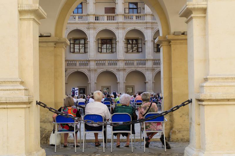 Rentner sitzen auf Klappstühlen bei einem Konzert im Innenhof des Landhauses