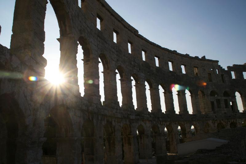 Sonnenuntergang hinter den Bögen der römischen Arena von Pula