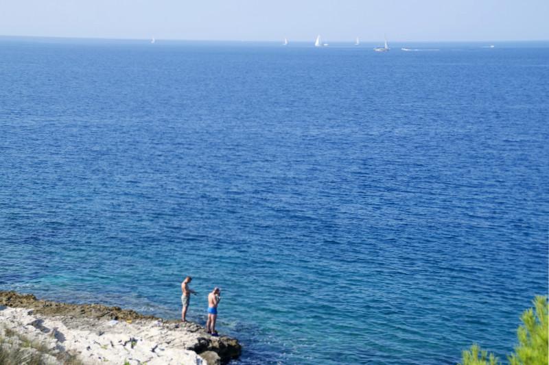 Zwei Männer stehen an der tiefblauen Adria