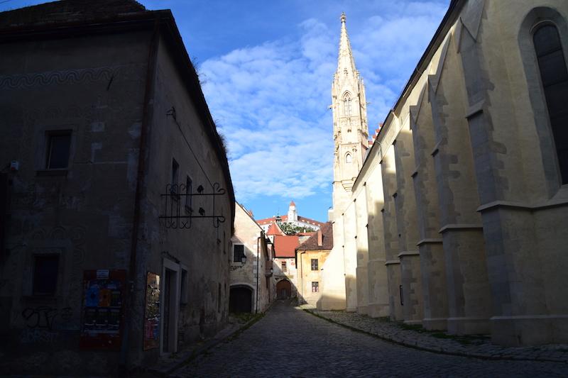 Rechts eine alte Kirche, in der Ferne die Burg von Bratislava