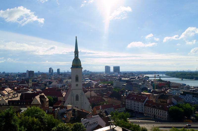 Panorama von Bratislava mit der Altstadt im Vordergrund, dahinter moderne Hochäuser und darüber blauer Himmel; rechts die Donau