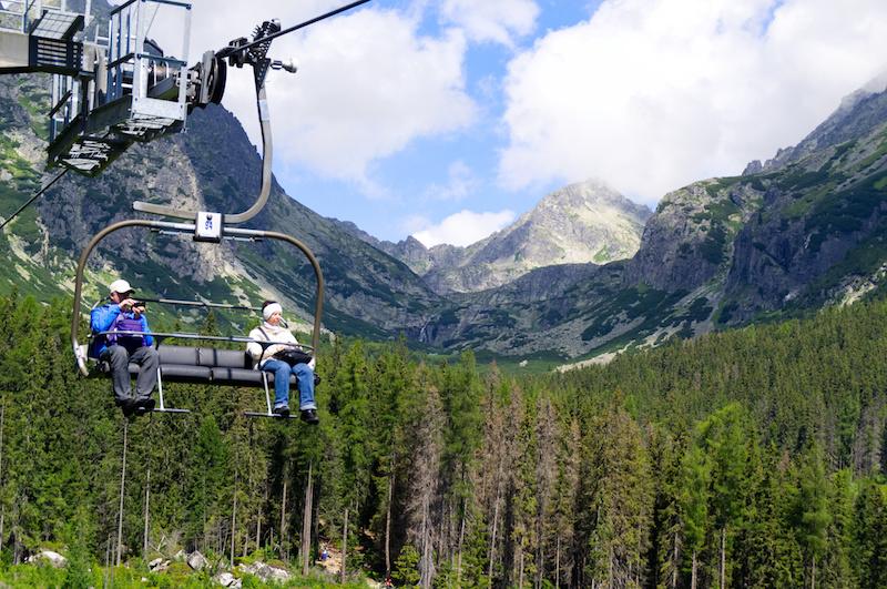 Ein älteres Paar sitzt in einem Sessellift vor dem Panorama der Hohen Tatra