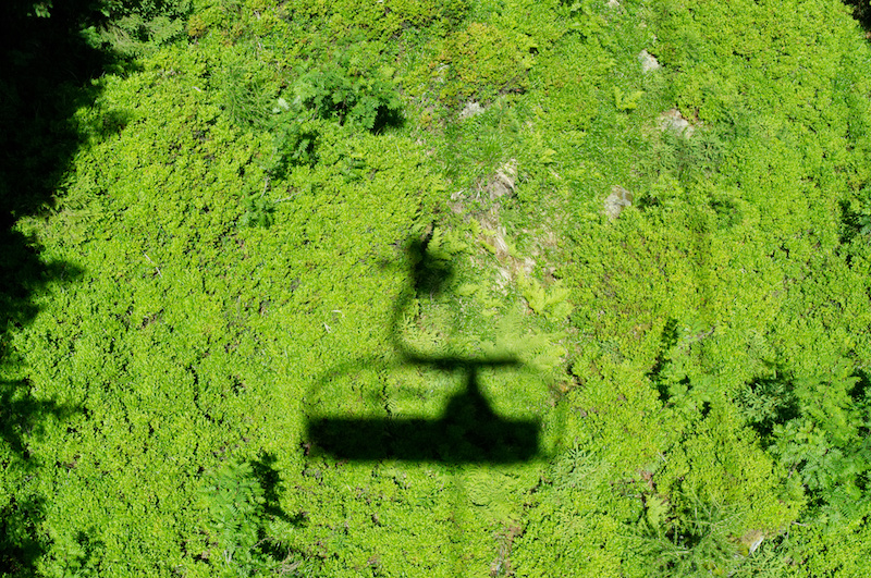 Der Sessellift wirft einen dunklen Schatten auf der grünen Wiese unter mir