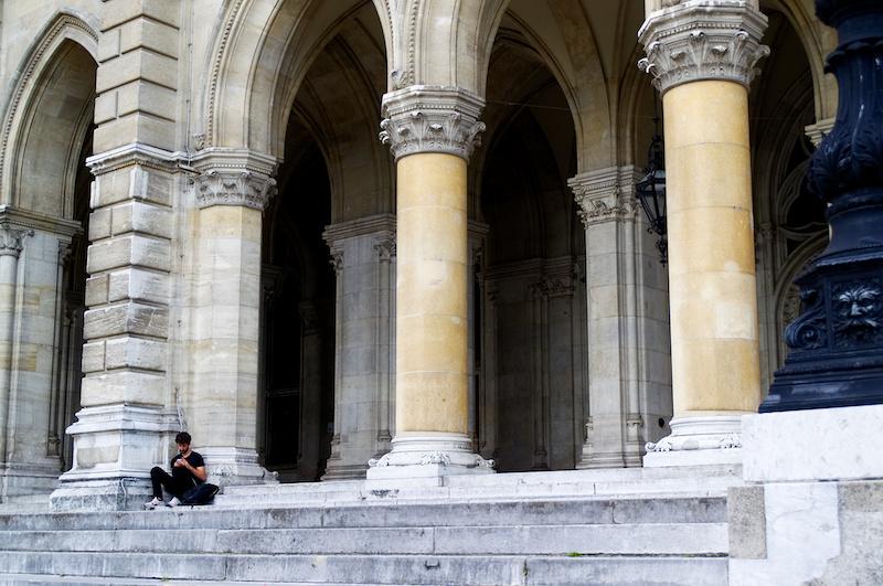 Ein junger Mann sitzt auf den Stufen vor dem Rathaus von Wien