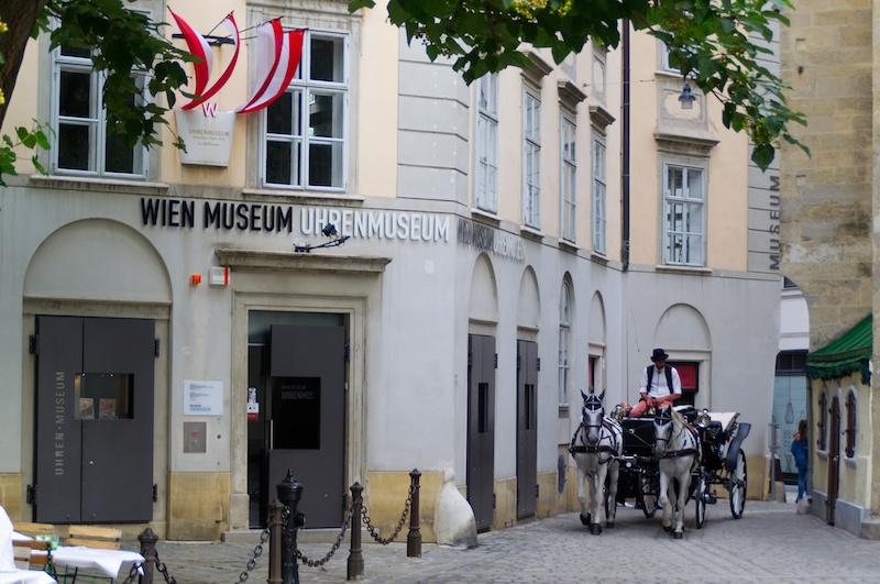 Eine Kutsche mit zwei weißen Pferden in eine der Gassen von Wien