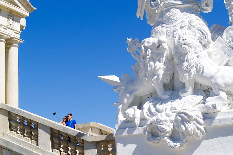 Zwei asiatische Touristen mit Selfie-Stick im Schlosspark von Schönbrunn