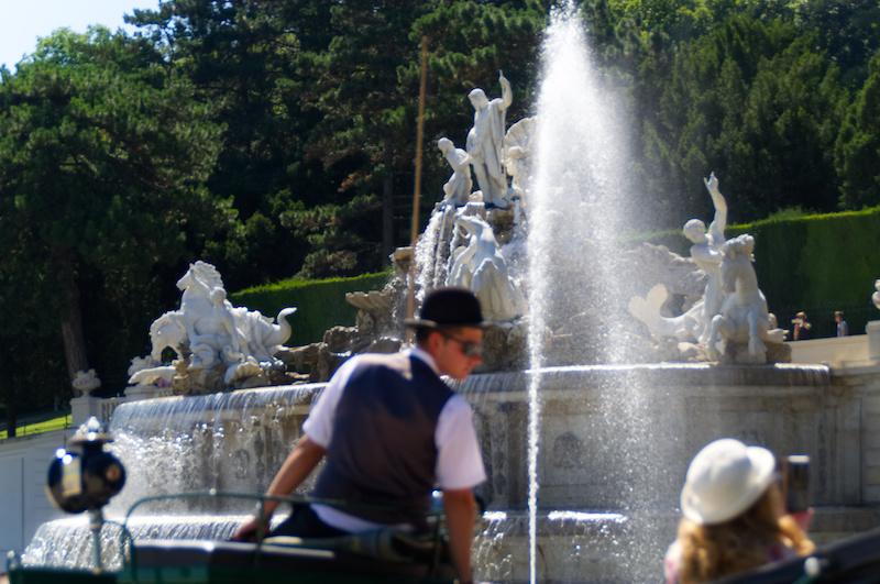 Die große Fontäne, davor ein Kutscher, im Schlosspark Schönbrunn