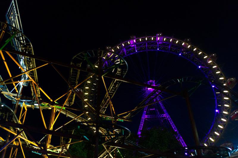 Achterbahn und das bekannte Riesenrad des Wiener Praters bei Nacht