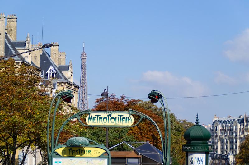 Ein Metro-Eingang mit Eiffelturm im Hintergrund