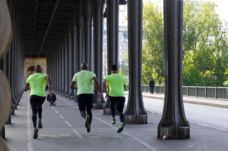 3 junge Männer in den gleichen Sport-Outfits rennen über die Brücke bei Bir Hakeim einem Fotografen entgegen