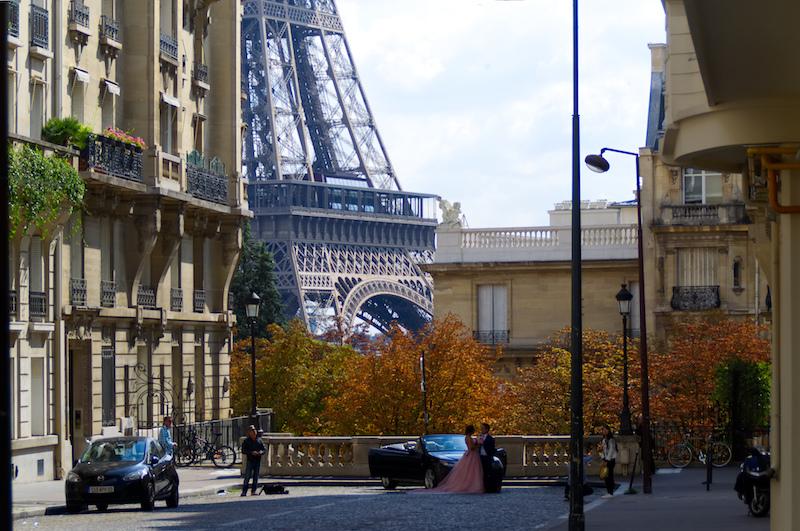 Ein Brautpaar lässt mit Eiffelturm als Kulisse Hochzeitsfotos schießen