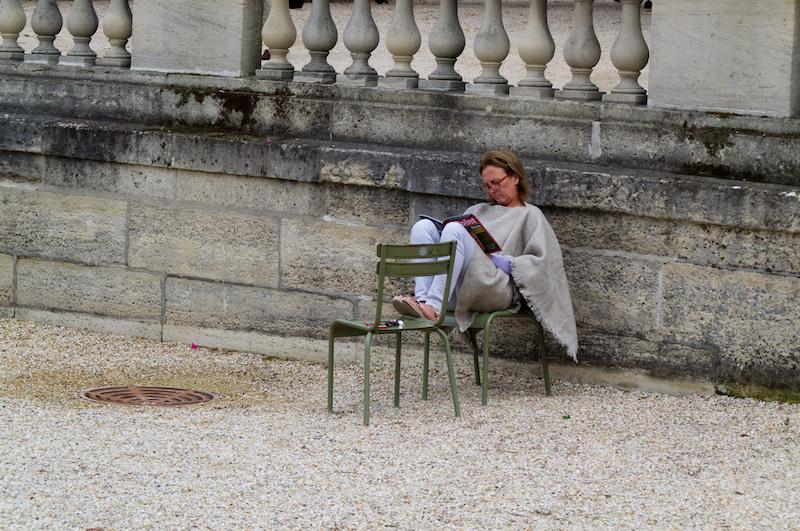 Eine Dame liest auf zwei Stühlen sitzend im Jardin du Luxembourg ein Magazin