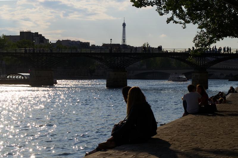 Menschen sitzen an der Seine, mit Eiffelturm im Hintergrund
