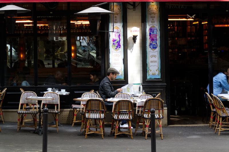 Ein junger Mann sitzt Zeitung lesend an einem Pariser Bistro-Tisch