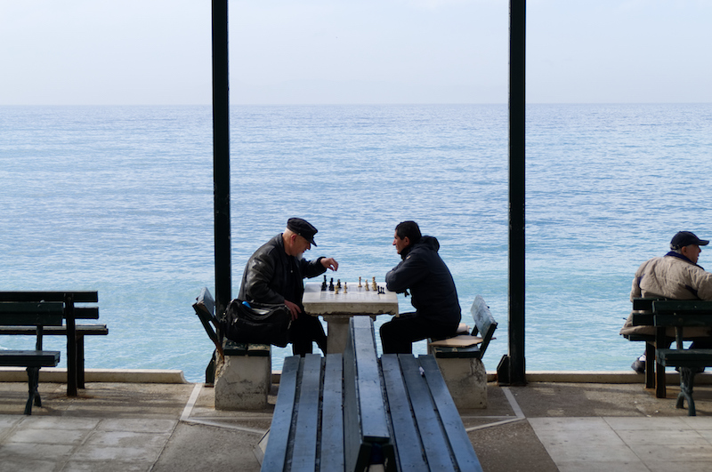 Zwei Männer spielen Schach am Strand von Athen