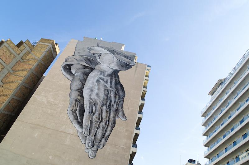 Betende Hände auf einer Häuserwand in Athen