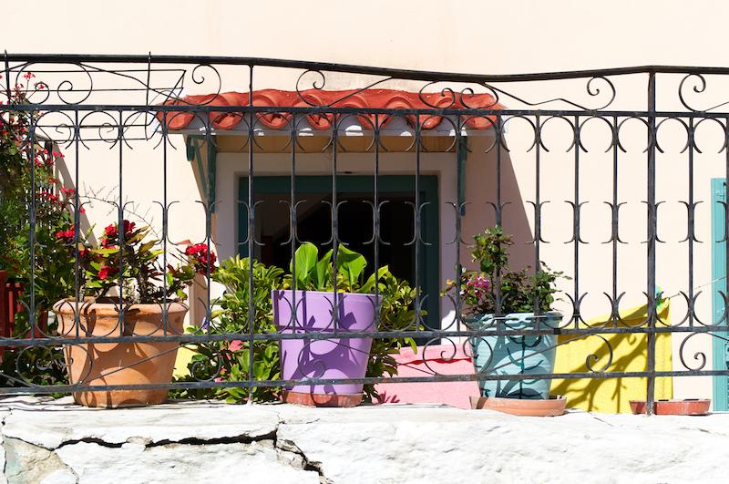 Blumentöpfe vor einem kleinen rosa Haus in Athen