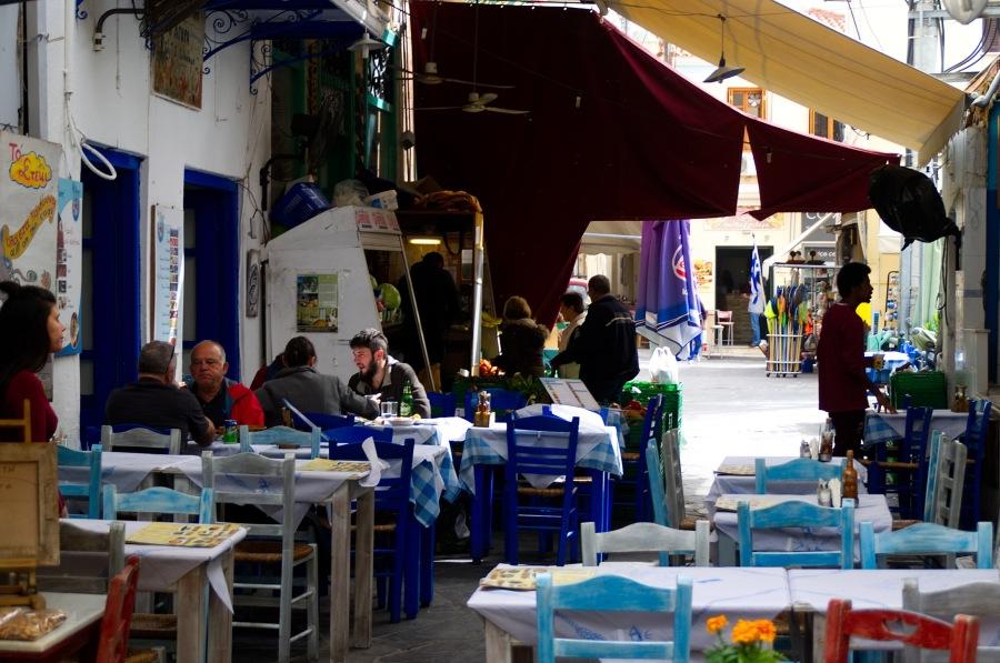 Eine kleine Taverne mit Menschen in den Gassen von Ägina