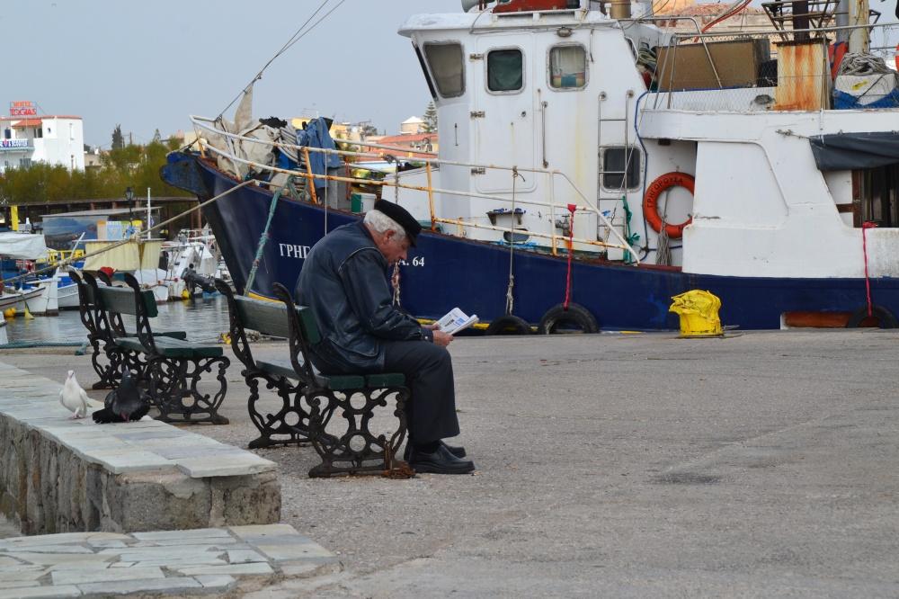 Ein alter Mann liest am Hafen von Ägina Zeitung