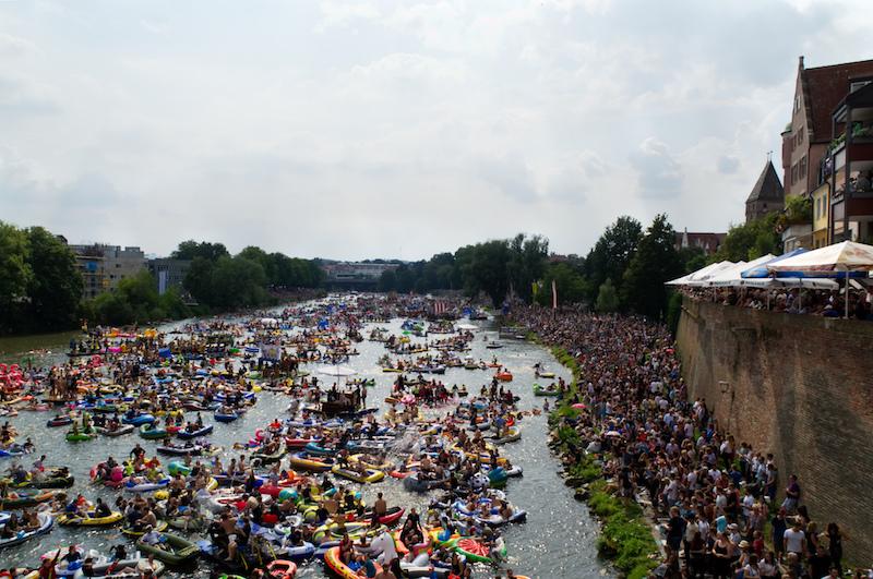 Boote auf der Donau und zehntausende Zuschauer auf den Wegen und der Stadtmauer in Ulm beim Nabada