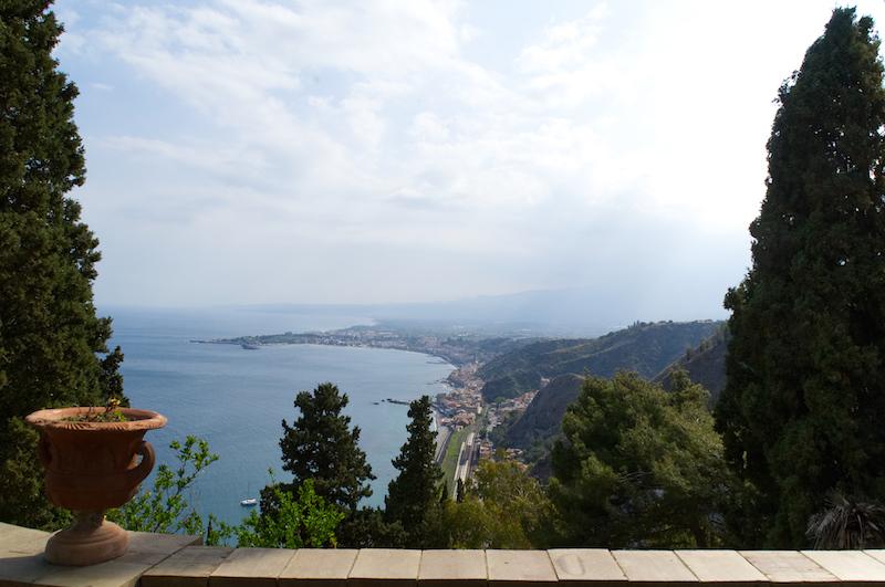 Von einer Terrasse in Taormina überblickt man die Bucht bis Catania und zum wolkenverhangenen Ätna