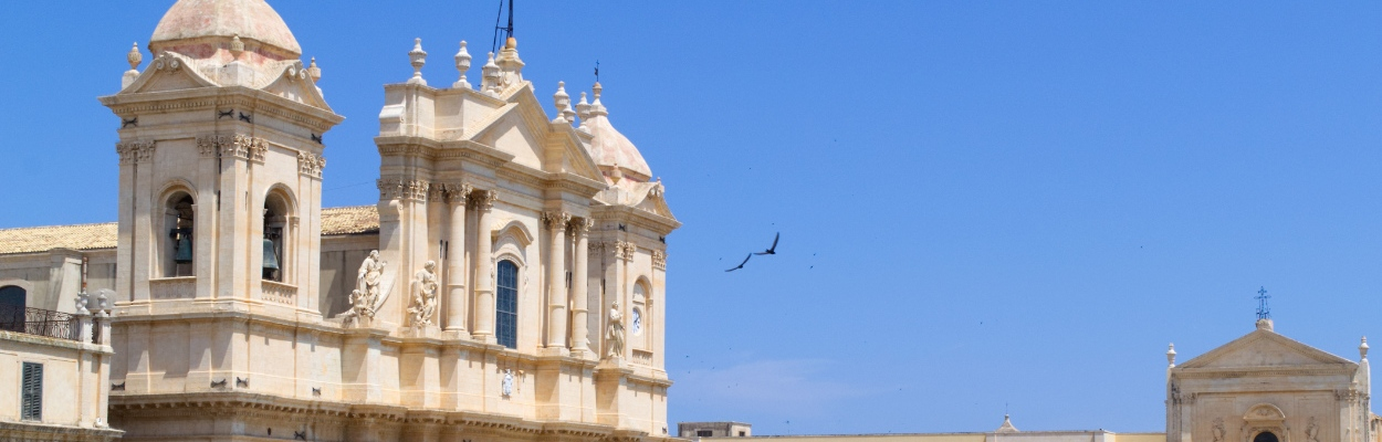 Schwalben fliegen über die Dächer von Noto, Sizilien