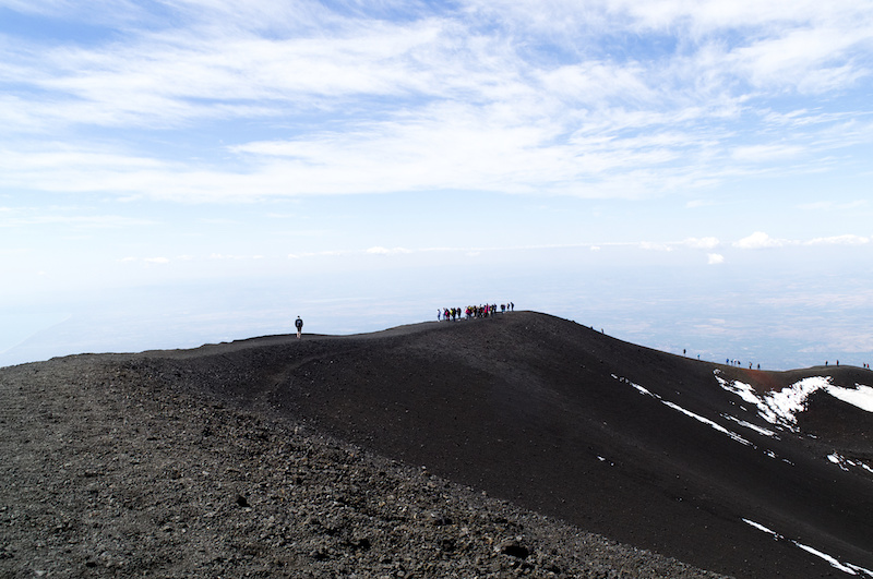 Besucher spazieren um den Krater des Ätna