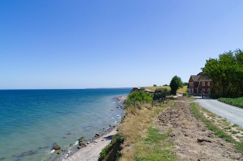 Küstenweg mit rotem Haus und viel Ostsee